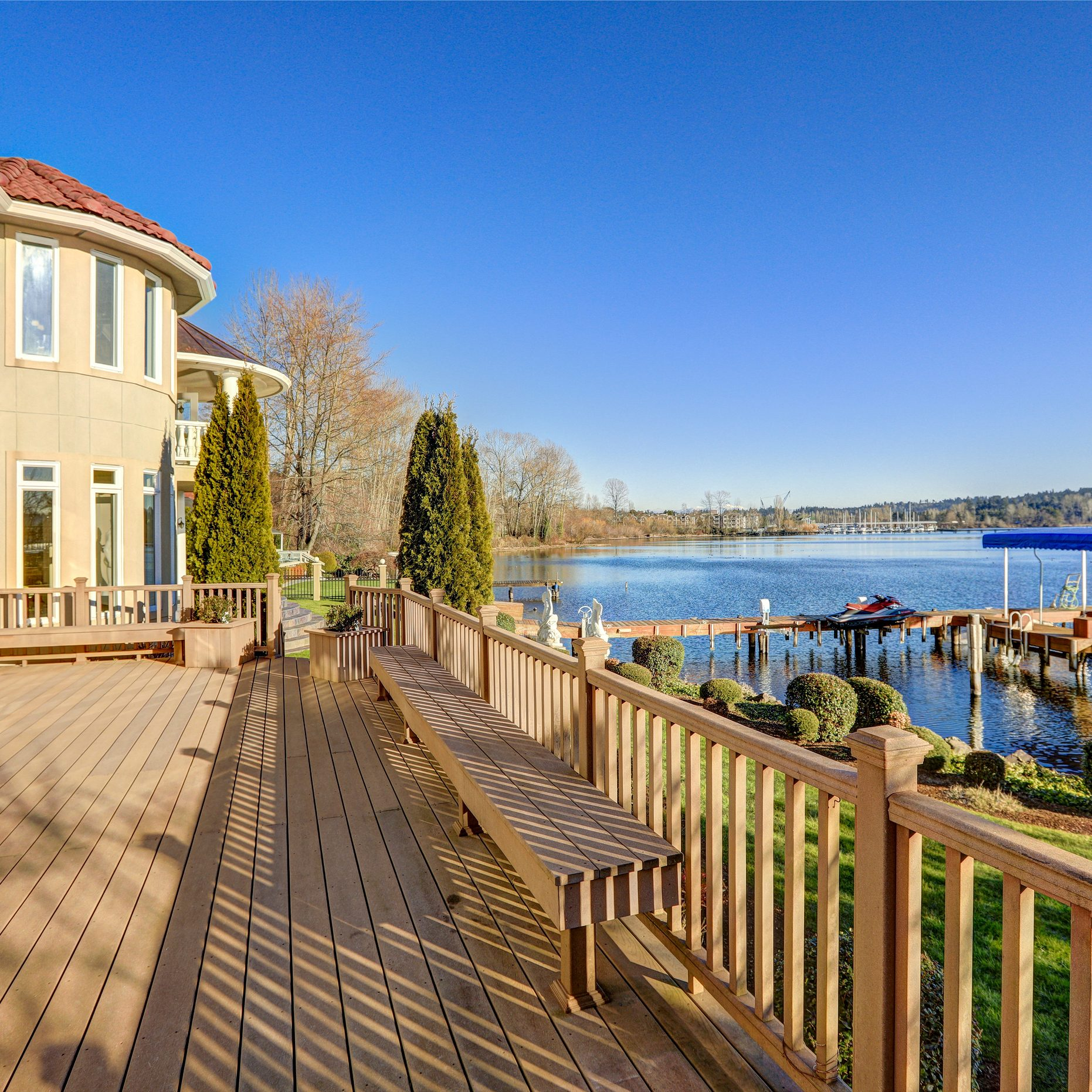 Sunny spacious walkout deck of luxurious Mediterranean style waterfront home overlooking picturesque view of Lake Washington. Northwest USA